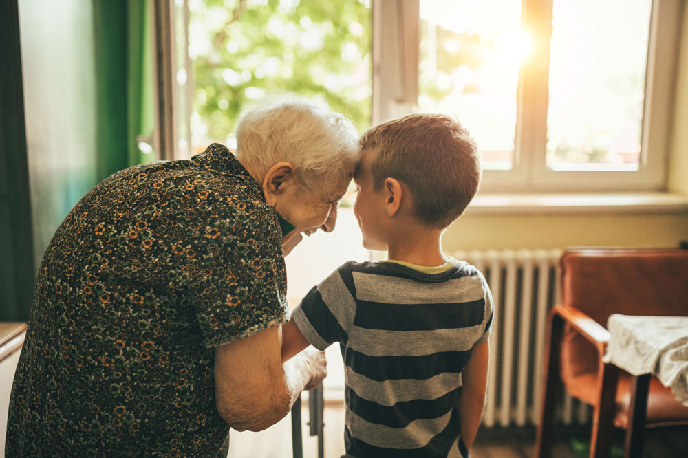 Charter Senior Living of Orland Park resident standing in doorway with young grandson