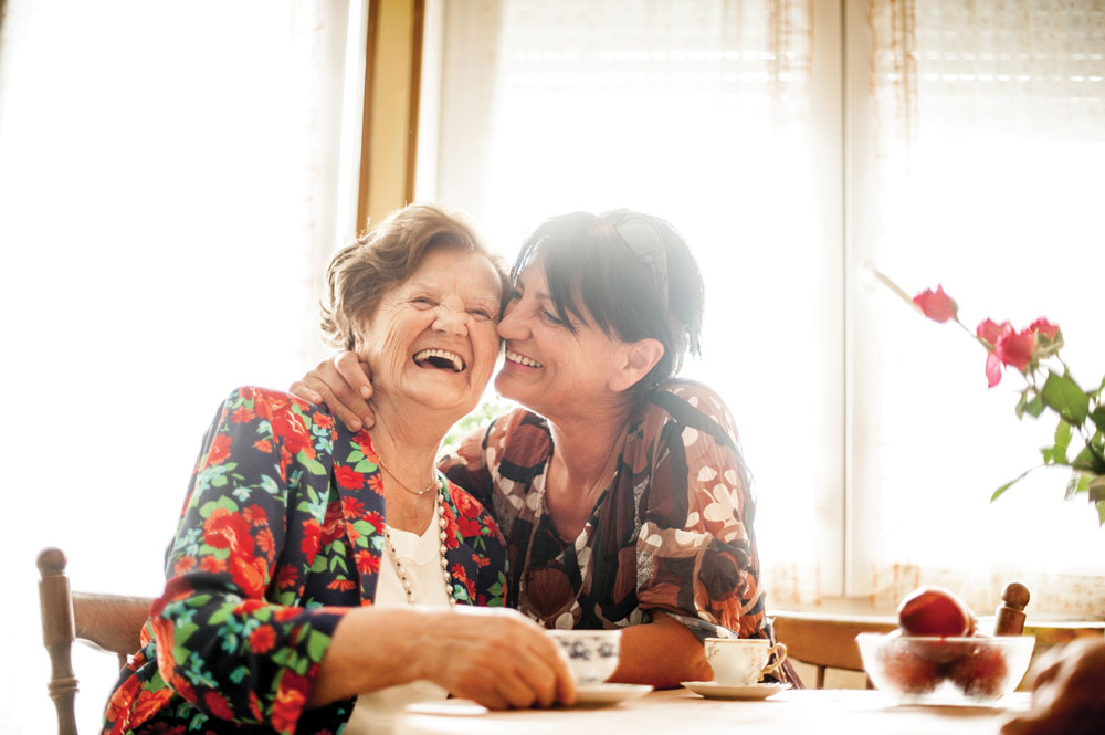 Senior living resident and her daughter laughing together at table